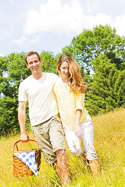 Couple walking with picnic basket on meadow, USA, New Jersey, Mendham