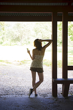 Woman texting on mobile phone standing in hut, USA, New Jersey, Mendham