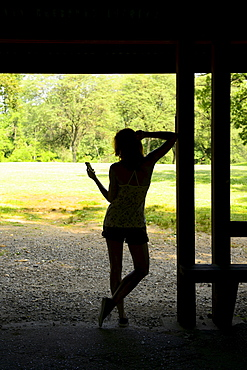 Silhouette of woman texting on mobile phone standing in hut, USA, New Jersey, Mendham