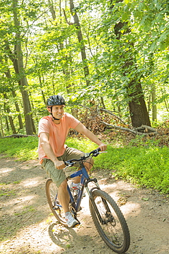 Man cycling in forest, USA, New Jersey, Mendham