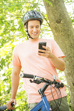 Man texting on mobile during bicycle trip, USA, New Jersey, Mendham