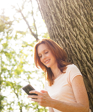 Woman leaning at tree and texting, USA, New Jersey, Mendham