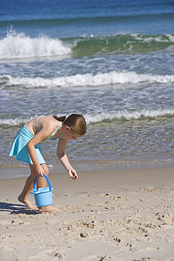 Girl collecting shells at beach