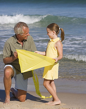 Father and daughter with kite at beach