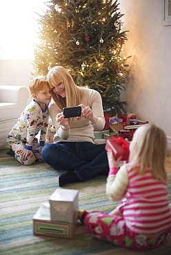 Mother with children (4-5, 6-7) opening christmas presents and taking photos