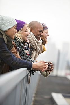 Friends standing on bridge and laughing