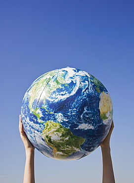 Person holding globe in air