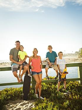 Portrait of happy family with three children (6-7, 10-11, 14-15) on beach, Laguna Beach, California