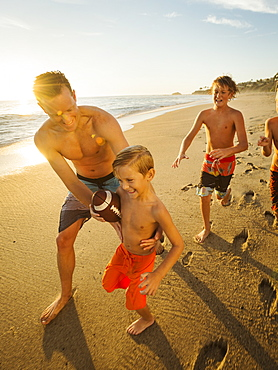 Father playing football on beach with his three sons (6-7, 10-11, 14-15), Laguna Beach, California