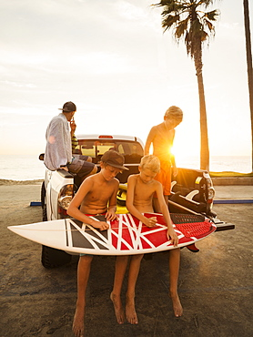 Boys (6-7, 10-11, 14-15) waxing surfboard at sunset, Laguna Beach, California