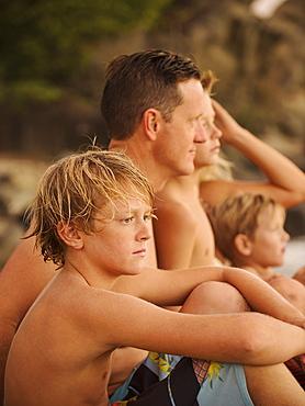 Family with three children (6-7, 10-11, 14-15) sitting on beach, Laguna Beach, California
