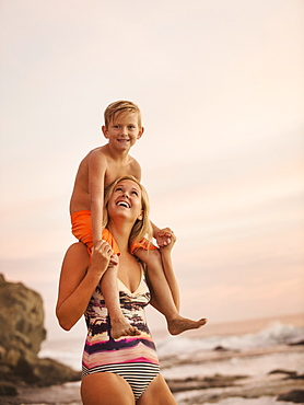 Mother carrying son (6-7) on shoulders outdoors, Laguna Beach, California