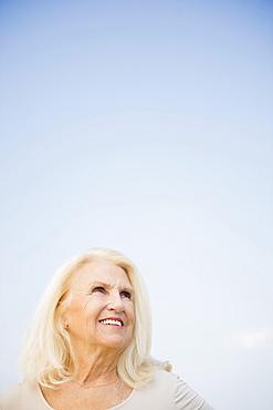 Portrait of senior woman against blue sky