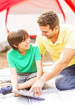 Father and son (12-13) using digital table at camping, Jupiter, Florida