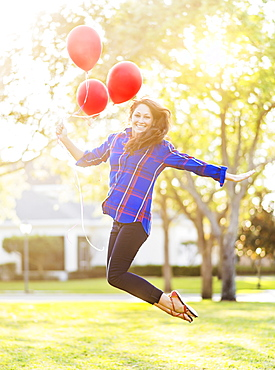 Woman holding balloons jumping, Jupiter, Florida
