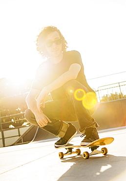 Man crouching on skateboard, West Palm Beach, Florida