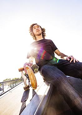 Skateboarder resting in skatepark, West Palm Beach, Florida