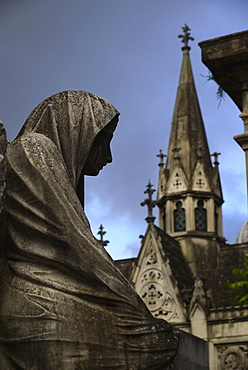 Close up of sculpture and church tower in Recoleta Cemetery, Recoleta Cemetery, Buenos Aires, Argentina