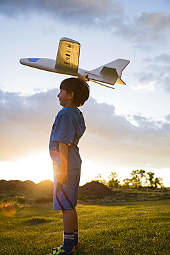 Boy (6-7) playing with model airplane outdoors, Colorado, USA