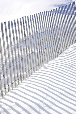 Shadow of fence on snow, New Jersey, USA