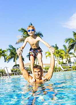 Boy (8-9) standing on brother's shoulders, Florida,USA