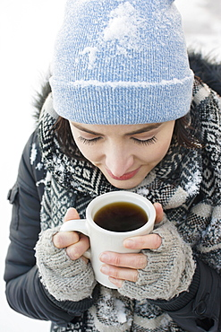 Woman with coffee mug in snow