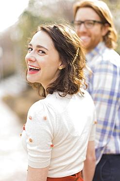 Young smiling woman next to boyfriend