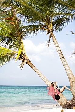 Woman relaxing on beach, Dominican Republic