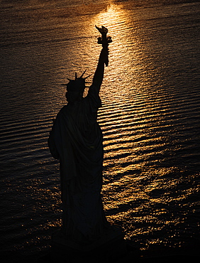USA, New York State, New York City, Silhouette of Statue of Liberty at sunrise