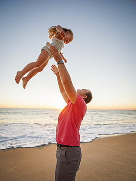 Father throwing daughter (4-5) in air on beach