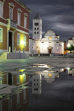 Croatia, Zadar, Buildings reflecting in puddle at dusk