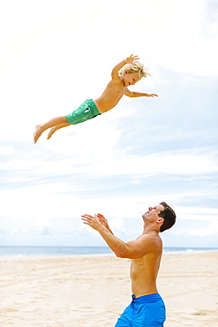 Father with son (4-5) playing at beach