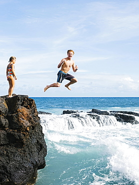 Girl (6-7) standing on cliff and man jumping into sea