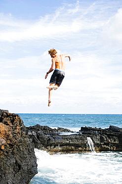 Young man jumping into sea