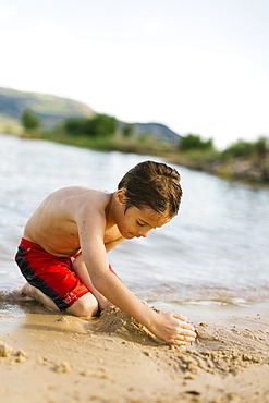Boy (6-7) playing on beach by lake