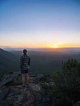Woman standing on peak of Blue Mountains at sunrise in New South Wales, Australia