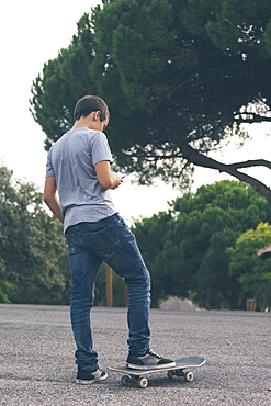 Young man texting while standing on skateboard