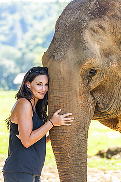 Woman holding trunk of Indian elephant in Chiang Mai, Thailand