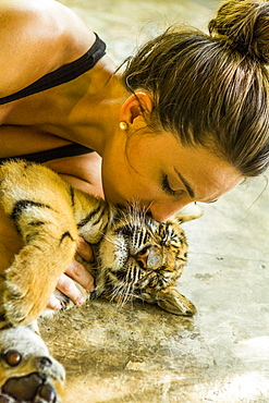 Woman kissing tiger cub