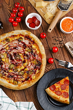 Pizza and ingredients on wooden table