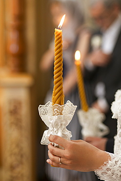 Hand of bride holding candle at wedding