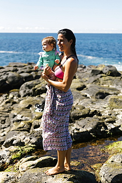 Woman holding baby daughter on rocks at beach