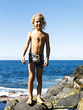 Boy standing on rocks at beach