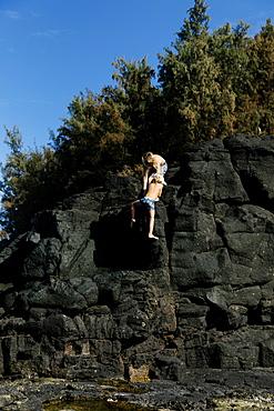Boys climbing cliff in swimwear