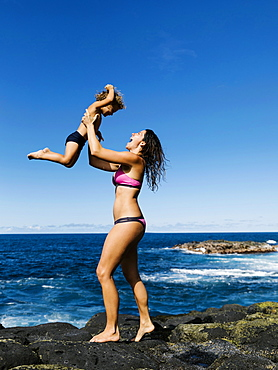 Mother lifting her son on rocks by sea