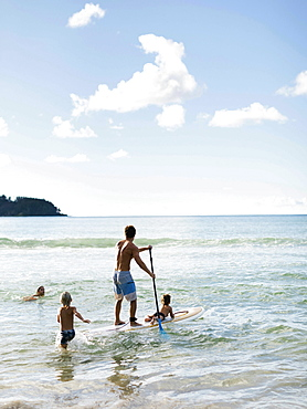 Man on paddleboard with his children at beach