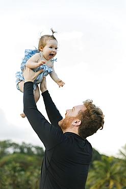 Man lifting baby daughter