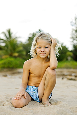 Blond haired boy kneeling on beach