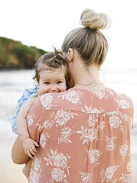 Woman holding baby daughter on beach