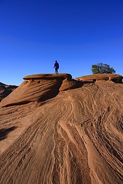 Woman walking on smooth rock in Monument Valley, Arizona, USA